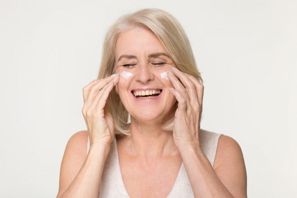 Mulher idosa de olhos fechados, em um fundo bege, com cabelos loiros bem claros na altura dos ombros. Ela passa creme hidratante em sua bochecha com suas mãos, demonstrando um cuidados para tipos de pele seca.