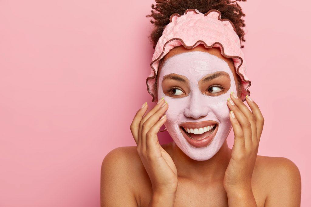 A imagem mostra uma mulher negra de tom claro, de cabelos cacheados avermelhados. O cabelo dela aparece preso com uma faixa rosa. Os ombros dela aparecem nus na foto, pois ela está em um momento de skincare. Em seu rosto, é possível ver uma máscara de argila rosa. Além disso, ela está sorrindo, olhando para o lado esquerdo e suas mãos estão massageando a face. Ao fundo, é possível ver uma parede rosa.